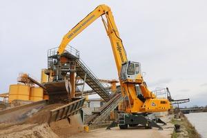 """<div class=""""bildtext"""">Die LZR GmbH setzt einen SENNEBOGEN 835&nbsp;E für den Sandumschlag und die Anlagenbeschickung ein • A SENNEBOGEN 835 E-series unit is used by LZR GmbH to handle sand and gravel and feed the processing facilities</div>"""