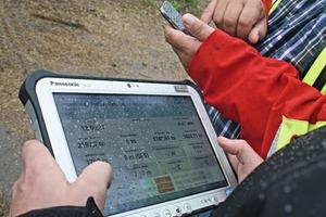 """<div class=""""bildtext"""">1 LeanManagement – Konsole: die PxKonsole zur Einsicht in den Materialzulauf. Robust und allen (feuchten) Widrigkeiten zum Trotz ist das Gerät für den Außeneinsatz bestens geeignet. Die Abbildung zeit die PxKonsole die am Fertiger angebracht wird. Der Polier hat Einsicht in den Materialzulauf in Echtzeit. Der Bauleiter ist via Smartphone im Bilde über den Baustellenverlauf # LeanManagement – Console: the PxKonsole providing insight into the material feed. Rugged and despite all (humid) weather conditions, the device is perfectly suitable for external use. The figure shows the PxKonsole, to be mounted at the paver. The foreman has real-time insight into the material feed. The site manager is informed about the construction process on site</div>"""