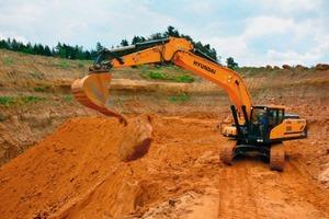 """1 In der Grube Dillberg in der Oberpfalz legt der Hyundai-Kettenbagger HX330NLC bei Sand-Adler große Brocken """"Doggersand"""" zur späteren Zerkleinerung ab"""
