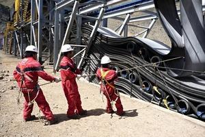 "4 Spezialisten positionieren und fixieren die Gurtschlaufen in der Kupfererzmine ""Los Pelambres"" # Experts while positioning and fixing the belt loops in the Los Pelambres copper ore mine"